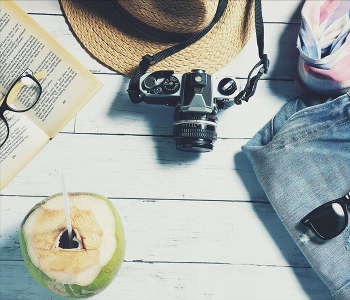 Wood flooring with books, glasses, hat, camera, clothes, and a vacation drink