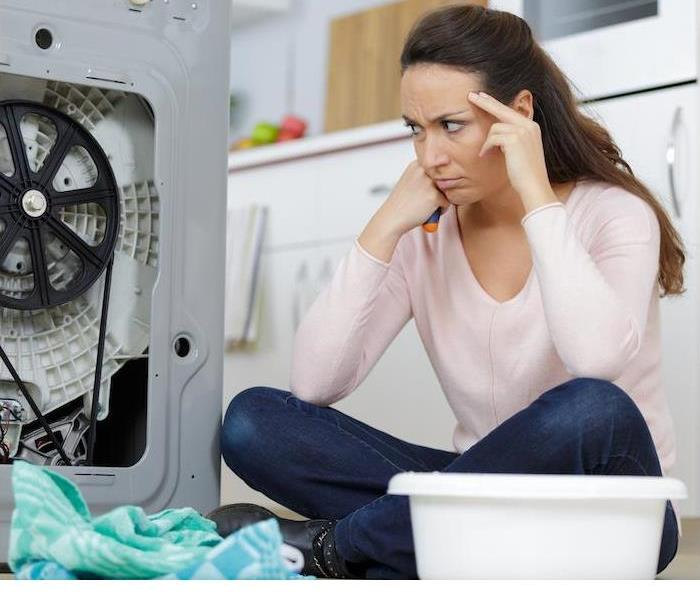 fustrated woman on floor looking at broken washer