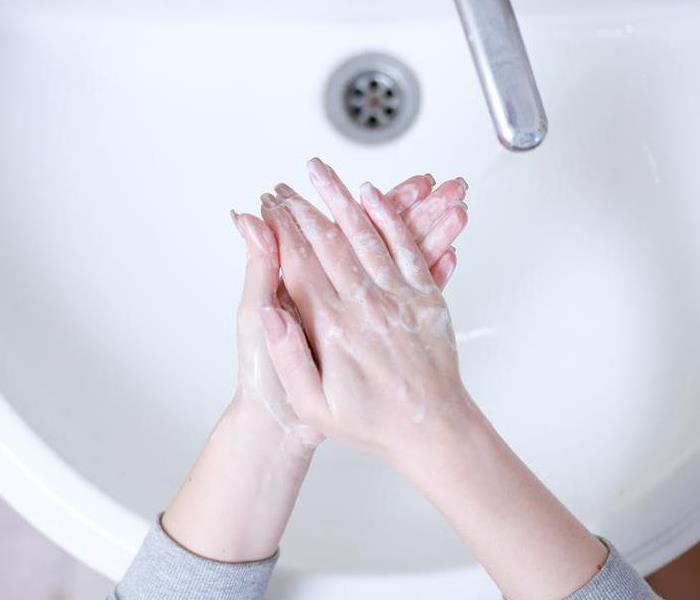 woman washing hands in a bathroom sink